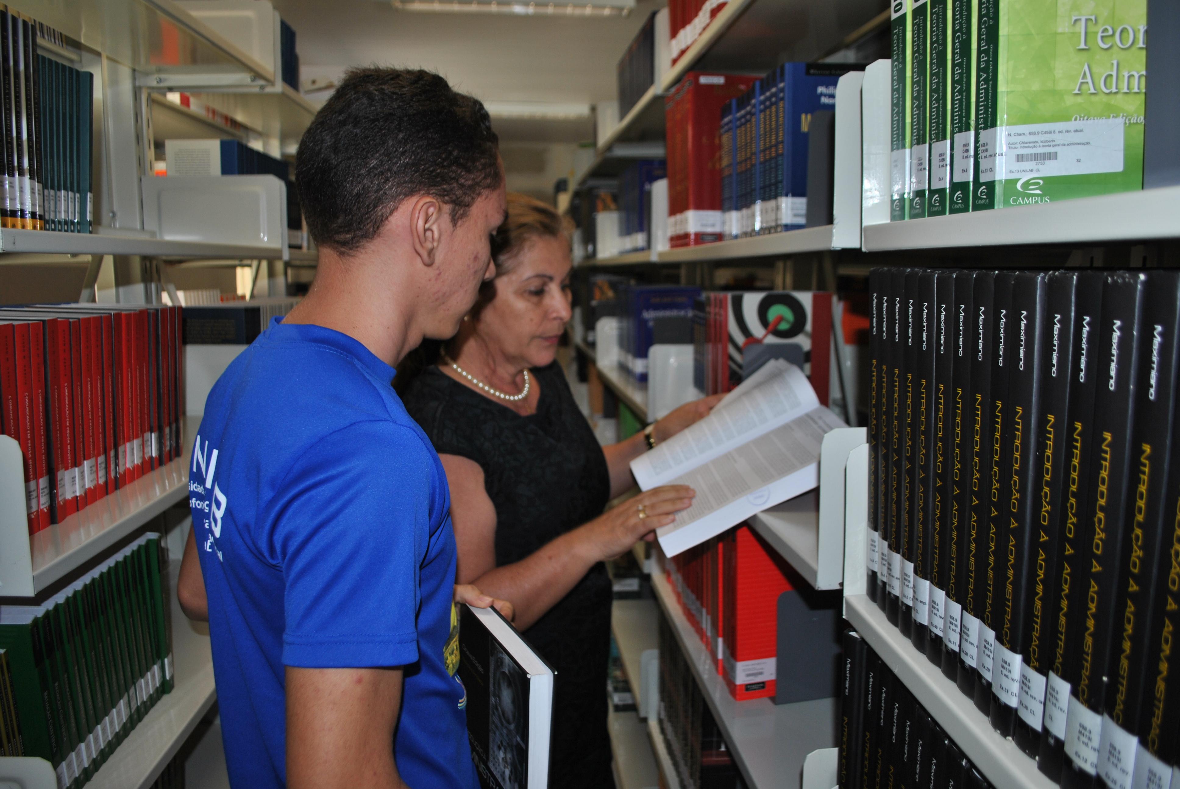 Coordenadora da Biblioteca, Fátima Portela, ao lado de estudante da Unilab.