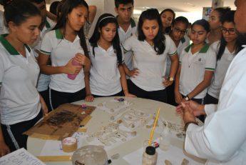Estudantes do Ensino Médio observam atentamente um experimento feito pelos estudantes de Curso de Química.