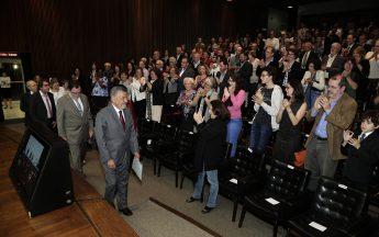 Tomaz Aroldo foi recebido de pé pela plateia e conduzido à mesa por um grupo de professores e técnicos-administrativos (Foto: Foca Lisboa / UFMG)